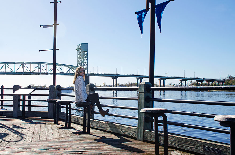 Leslie sitting on a bench at the waterfront in Wilmington North Carolina