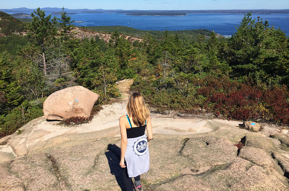 Leslie walking at the top of the Beehive Trail in Acadia National Park in Maine during our gap year