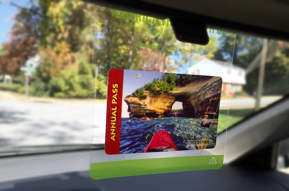 An annual National Park pass hanging from a car rearview mirror