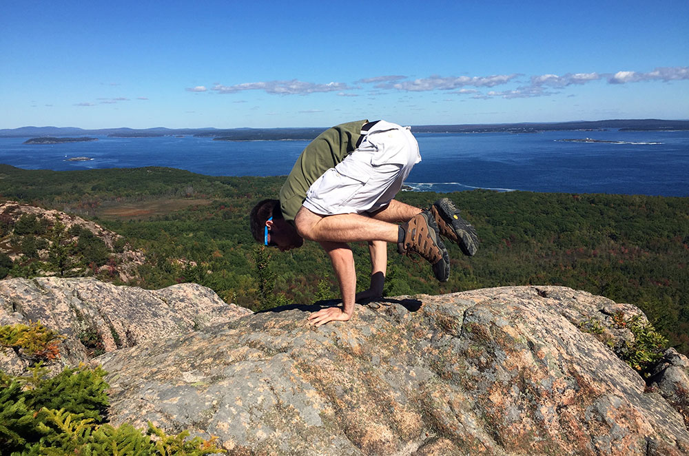 About Us: Brad doing a yoga Crow Pose in Acadia National Park
