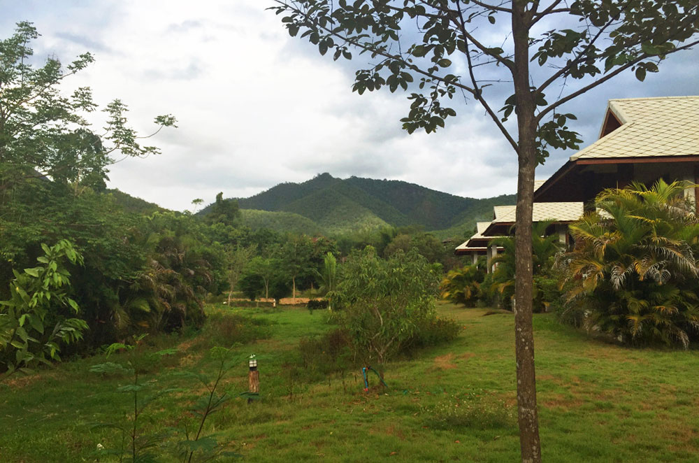 Buildings in the countryside of Pai Thailand with mountains in the background