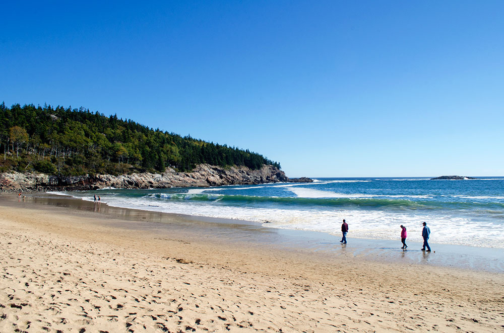 People walking along the water of Sand Beach in Acadia National Park