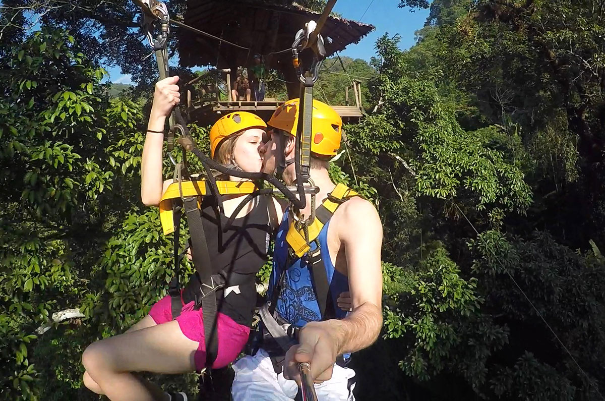 A couple kissing on the tandem zipline at Flight of the Gibbon in Chiang Mai