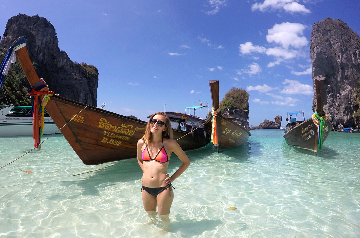 A girl standing in front of a longboat in the Phi Phi Islands of Thailand