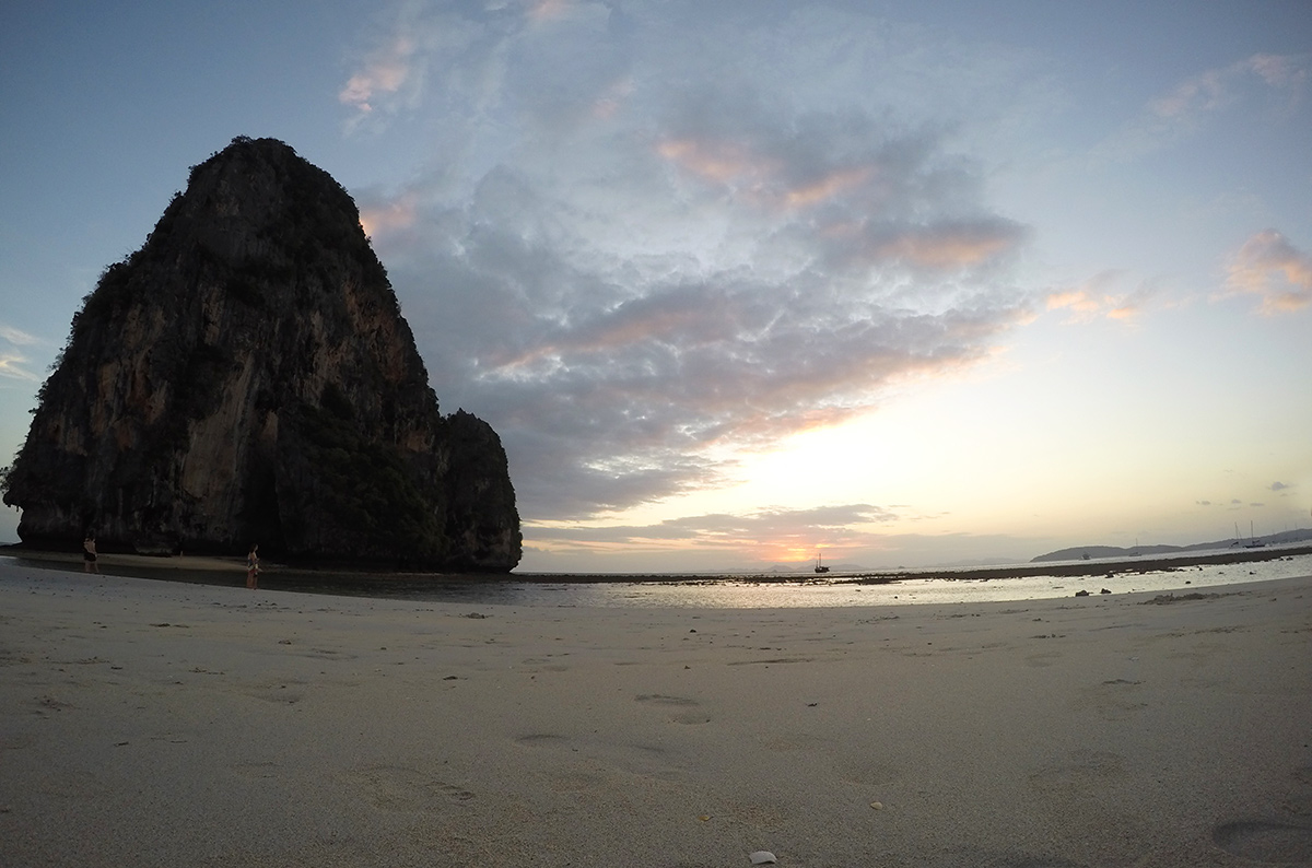 The sun setting behind a limestone island at Phra Nang Beach near Ao Nang Thailand