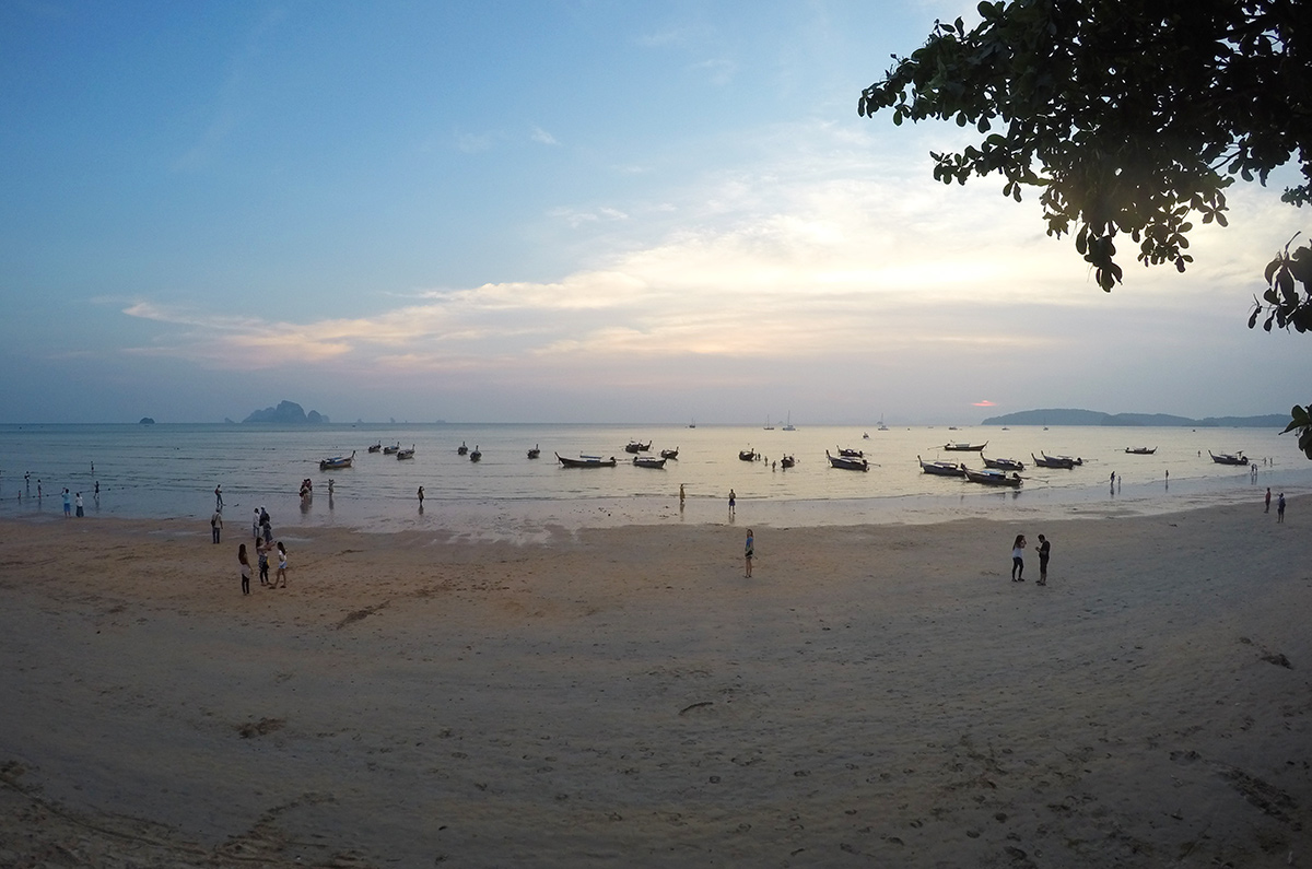 Many longboats docked at Ao Nang beach as the sun sets over the ocean in Aonang Thailand