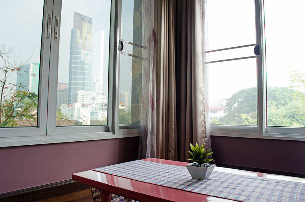 A small table in the corner of our Airbnb room with a nice view of Bangkok out the window