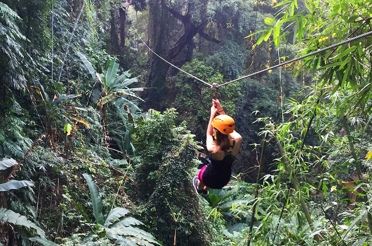 A girl riding a zipline at Flight of the Gibbon in Chiang Mai Thailand