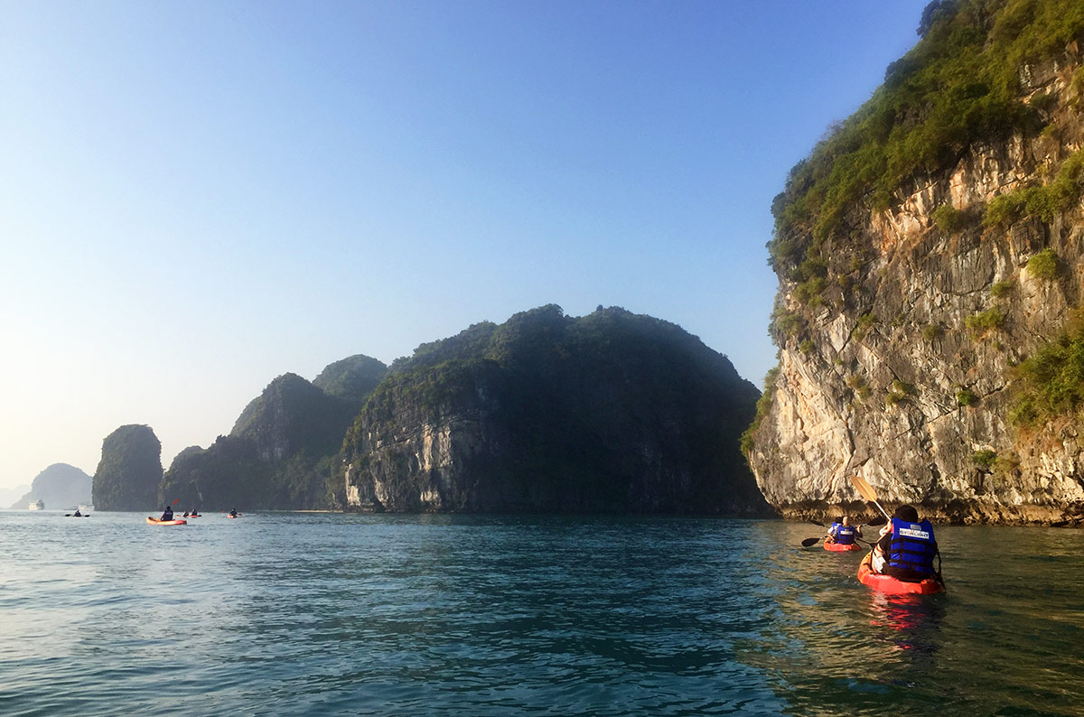 People kayaking in Halong Bay Vietnam during a weekend with Oriental Sails
