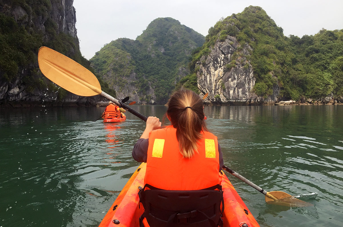 A girl from the Calypso Cruiser kayaking in Halong Bay Vietnam