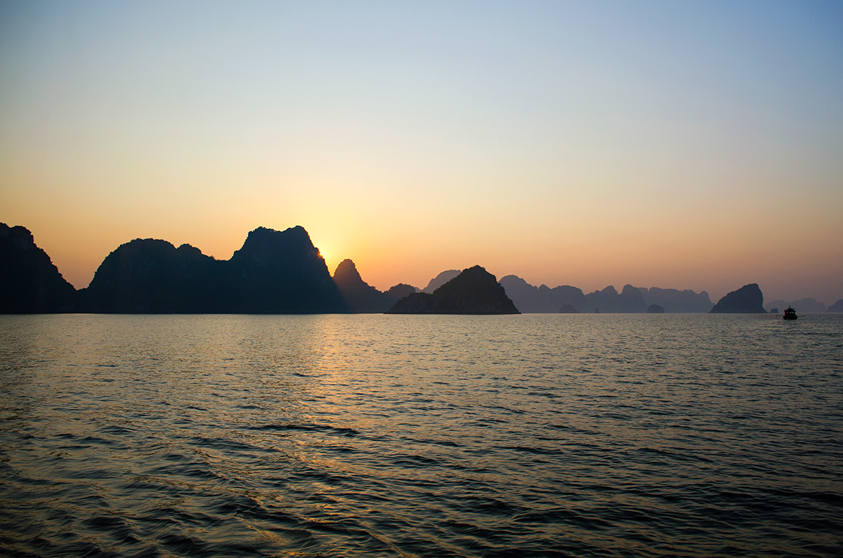 The sunsetting behind limestone islands in Halong Bay Vietnam