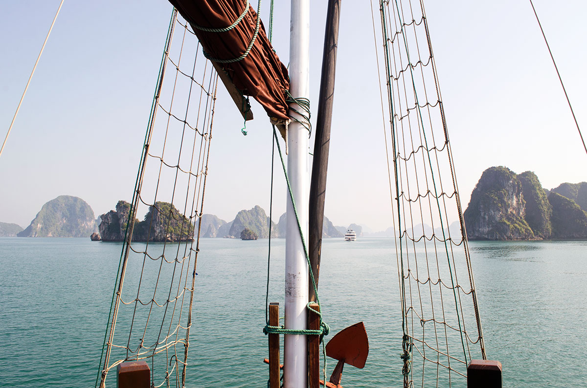 The bow of the Oriental Sails Calypso Cruiser sailing through Halong Bay
