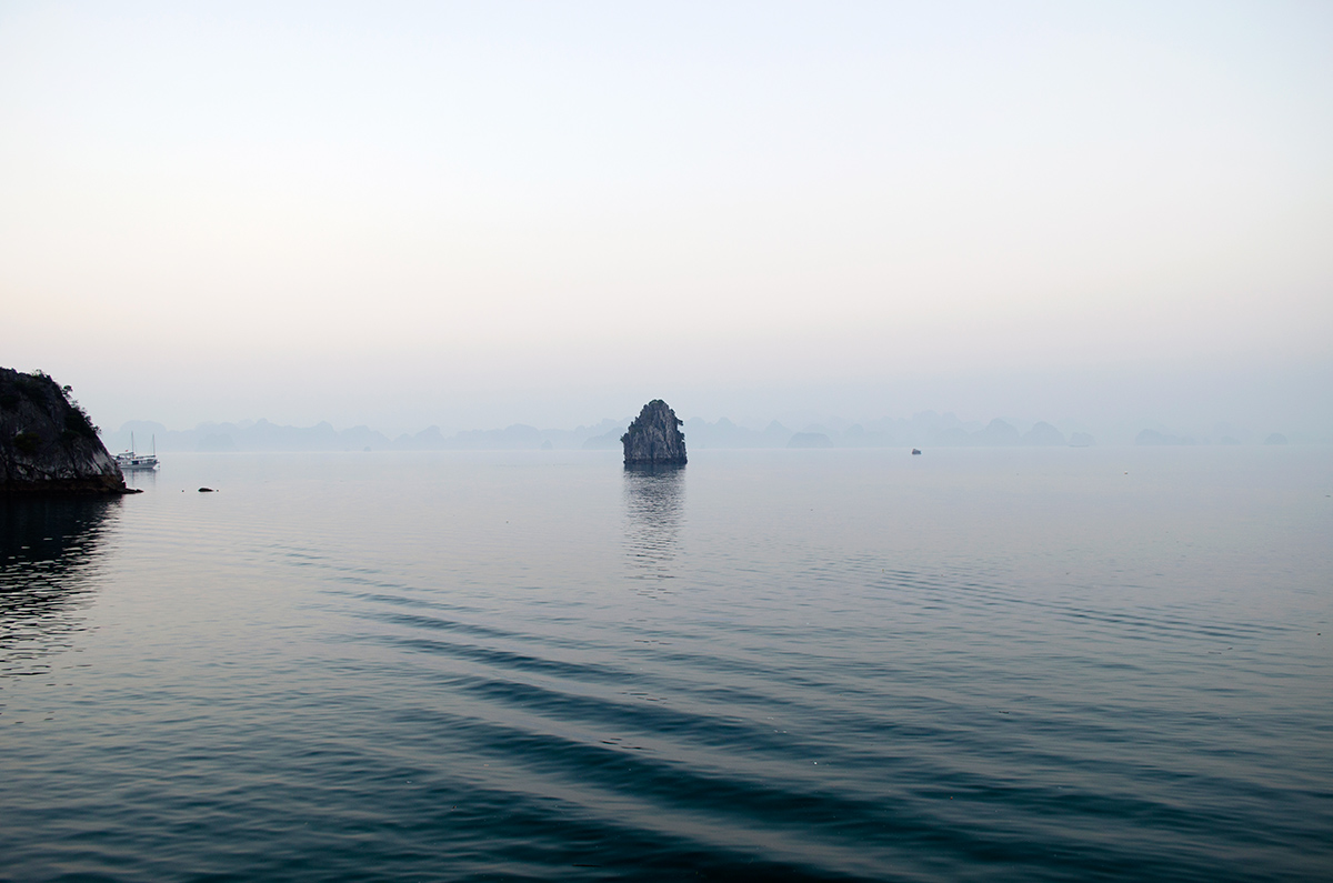 A boats wake causing ripples in the water of Halong Bay