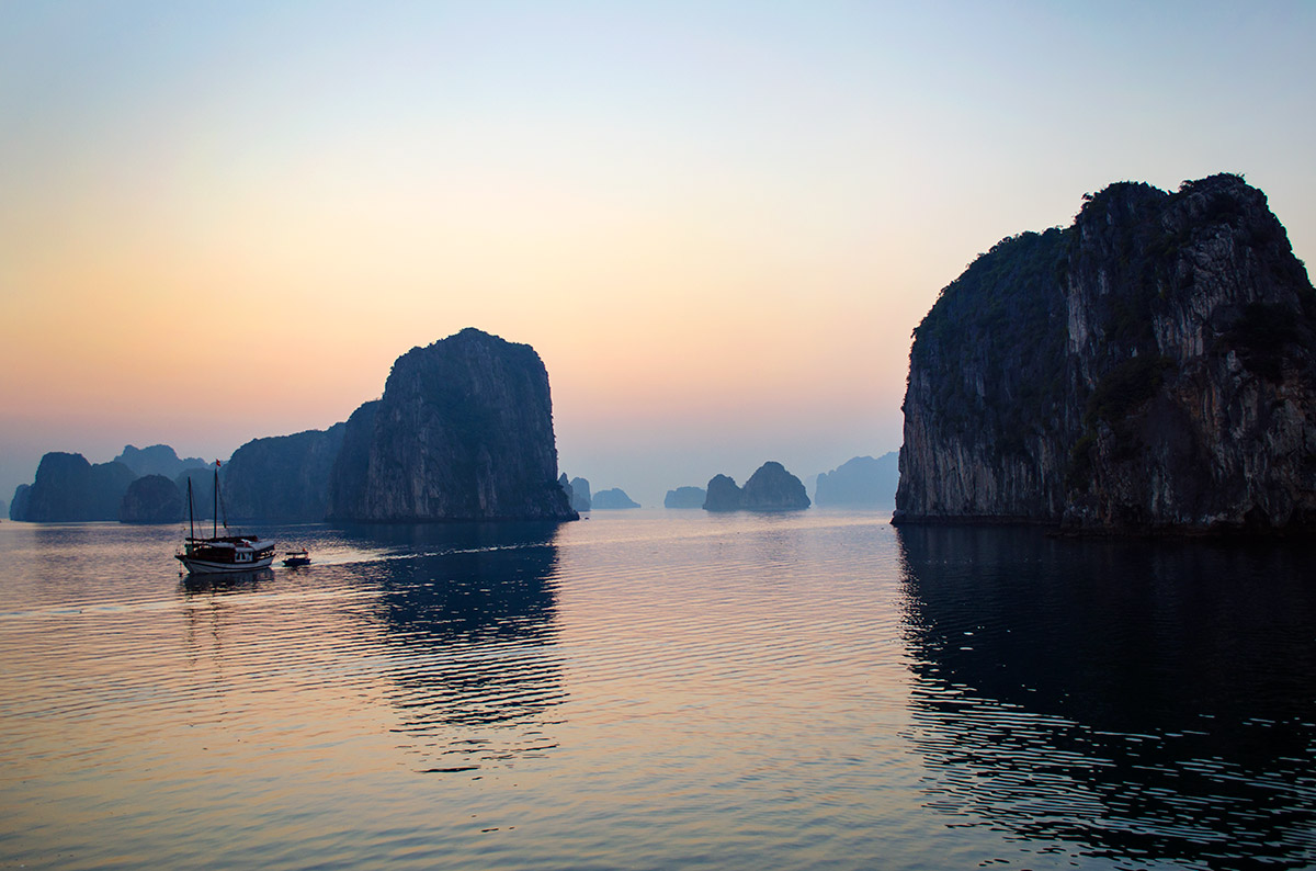 A colorful sky as the sunsets in front of islands in Halong Bay Vietnam