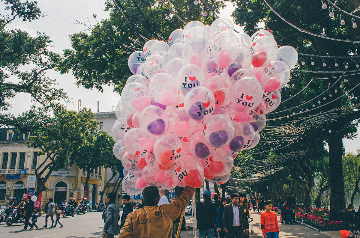 A vietnamses man selling balloons that say I love you in Hanoi