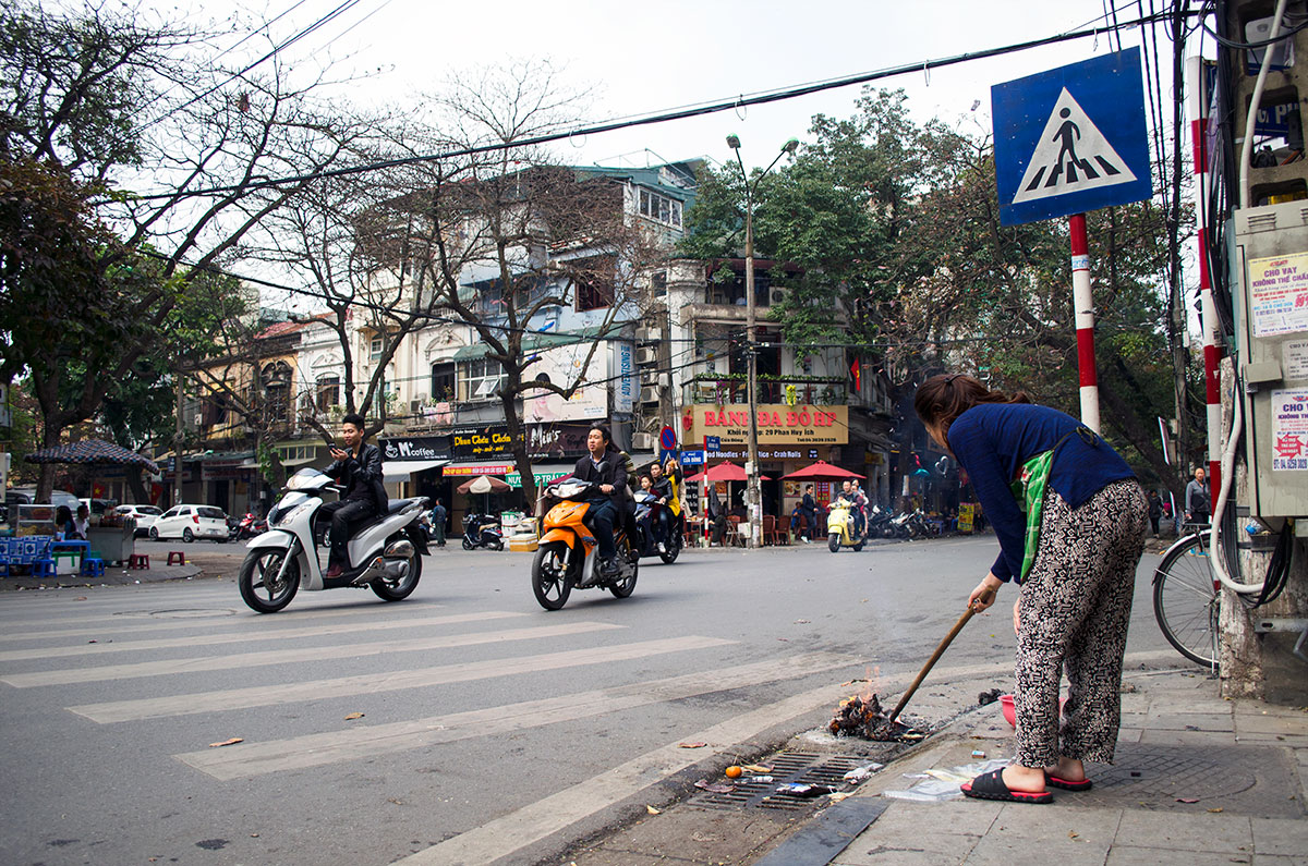 A Vietnamese lady burning ghost money in Hanoi Vietnam