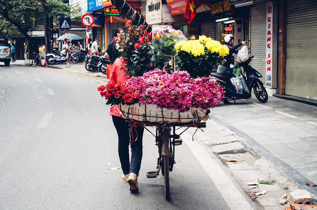 A girl selling flowers from her bike in Hanoi Vietnam