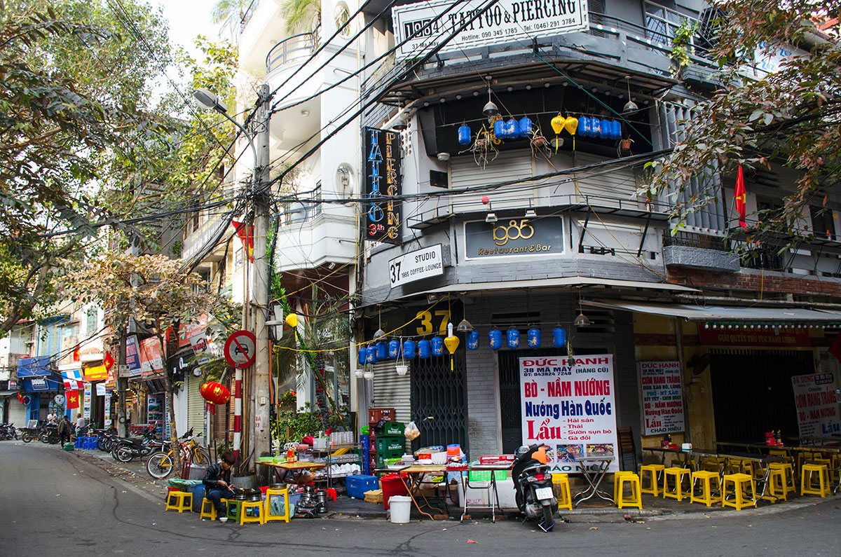 Many small yellow stools on the sidewalk meant for outdoor seating in Hanoi