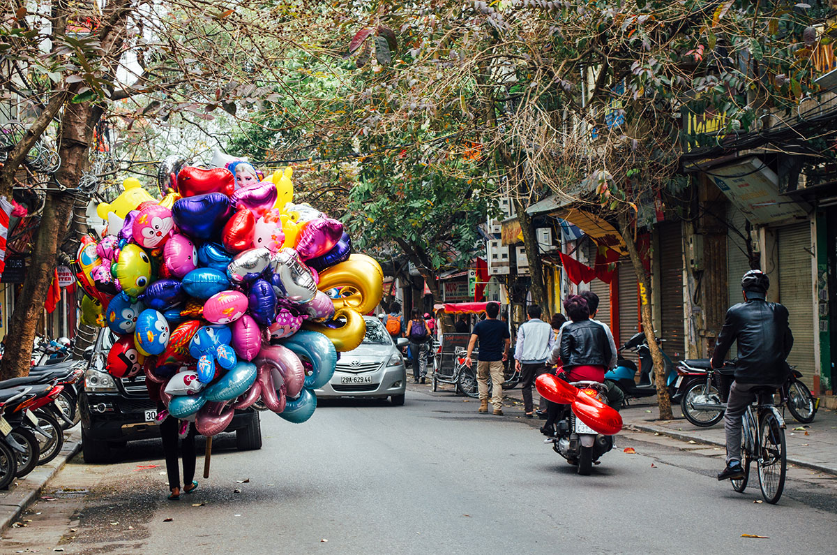 A vietnamese person selling balloons on a backstreet in Hanoi Vietnam