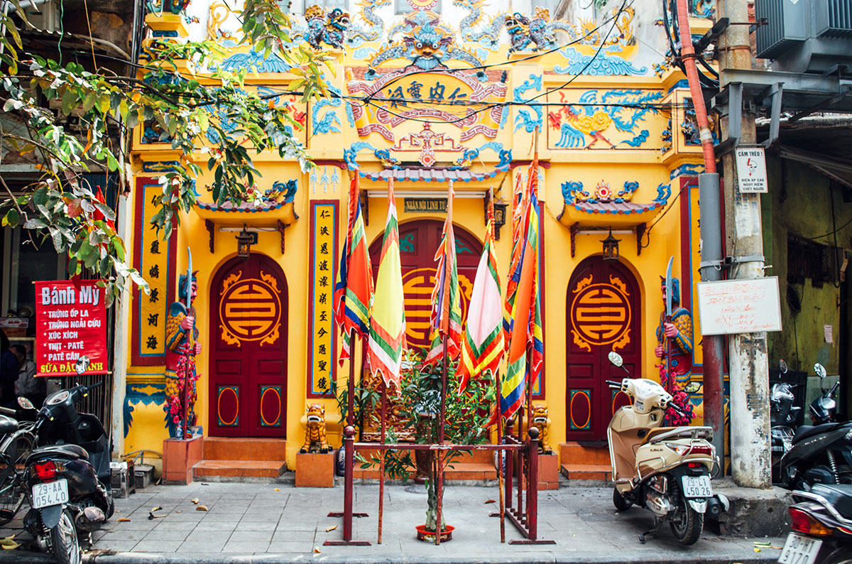 A bright yellow and red temple on a back street of Hanoi's old quarter