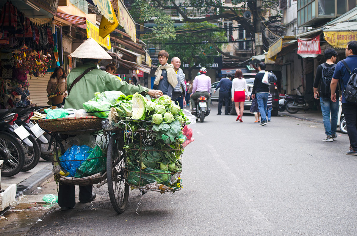 A lady selling vegetables from the back of a bicycle in Hanoi