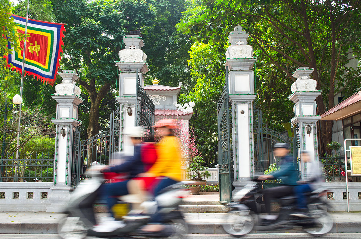 Blurred scooters driving past dihn nam huong temple near hoan kiem in Hanoi Vietnam