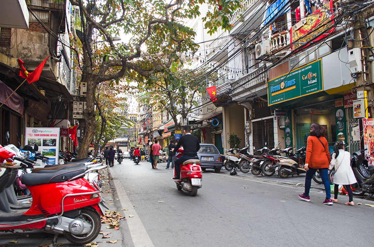 Someone driving a red scooter down a street in Hanoi