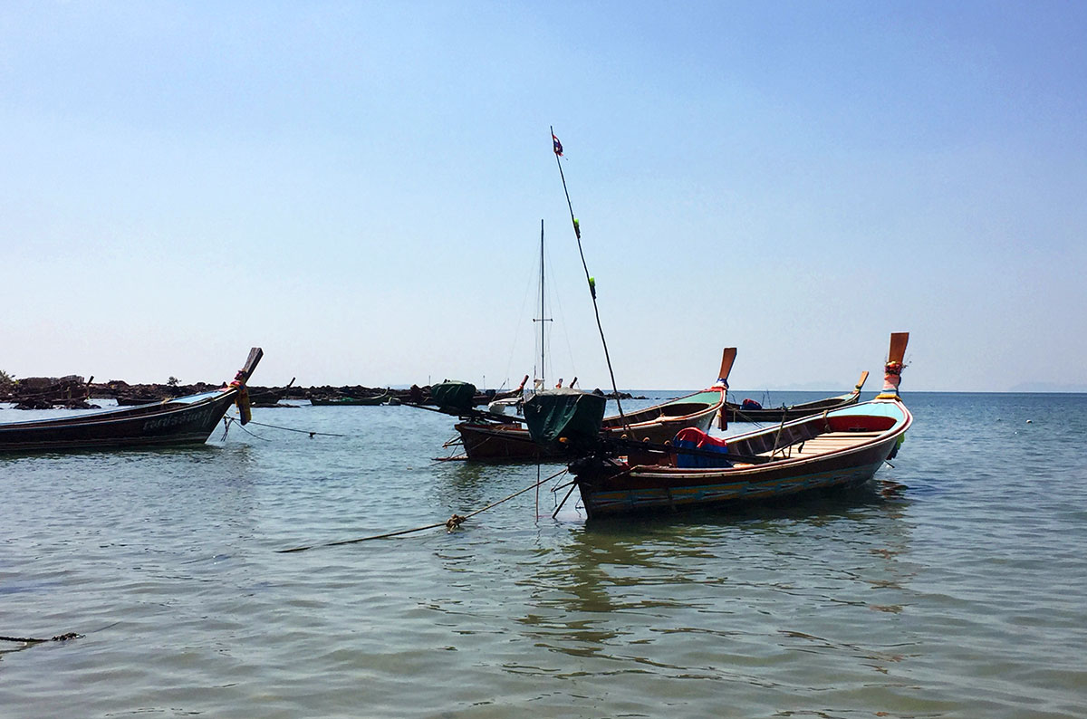 A closeup of three longboats in the waters of Koh Lanta