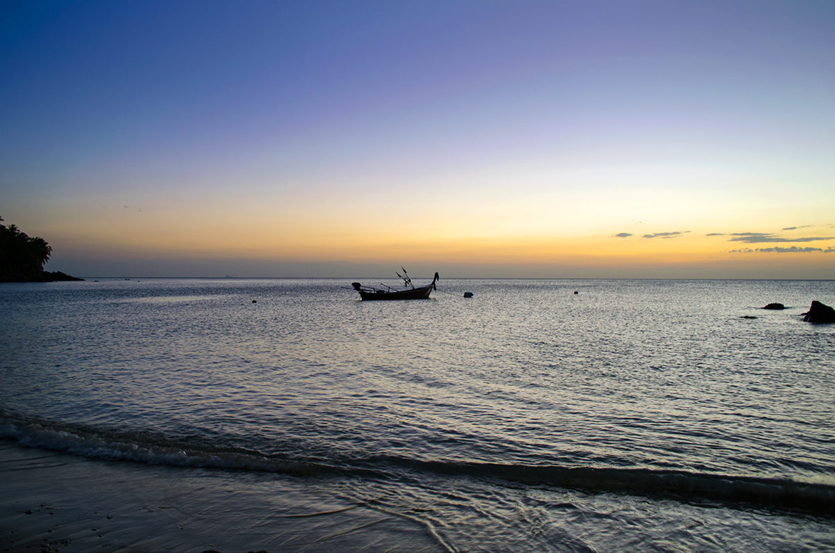 A longboat floating in the water as the sun sets over the ocean in Koh Lanta