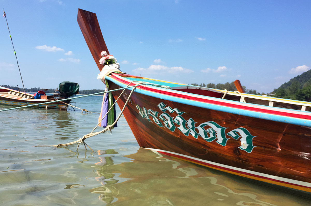 A closeup of a wooden longboat with Thai text on the bow in Koh Lanta