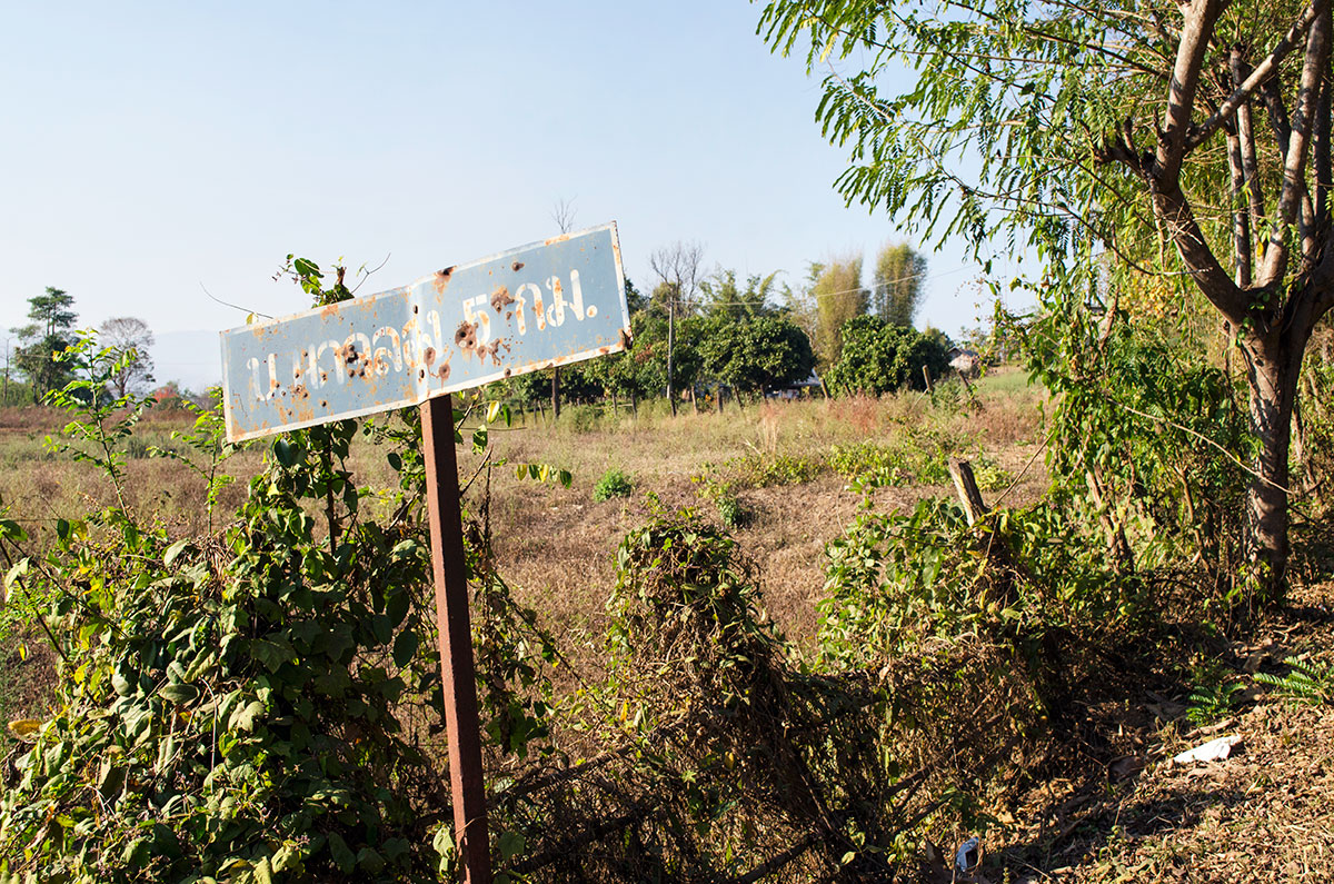A sign with bullet holes in the countryside of Pai