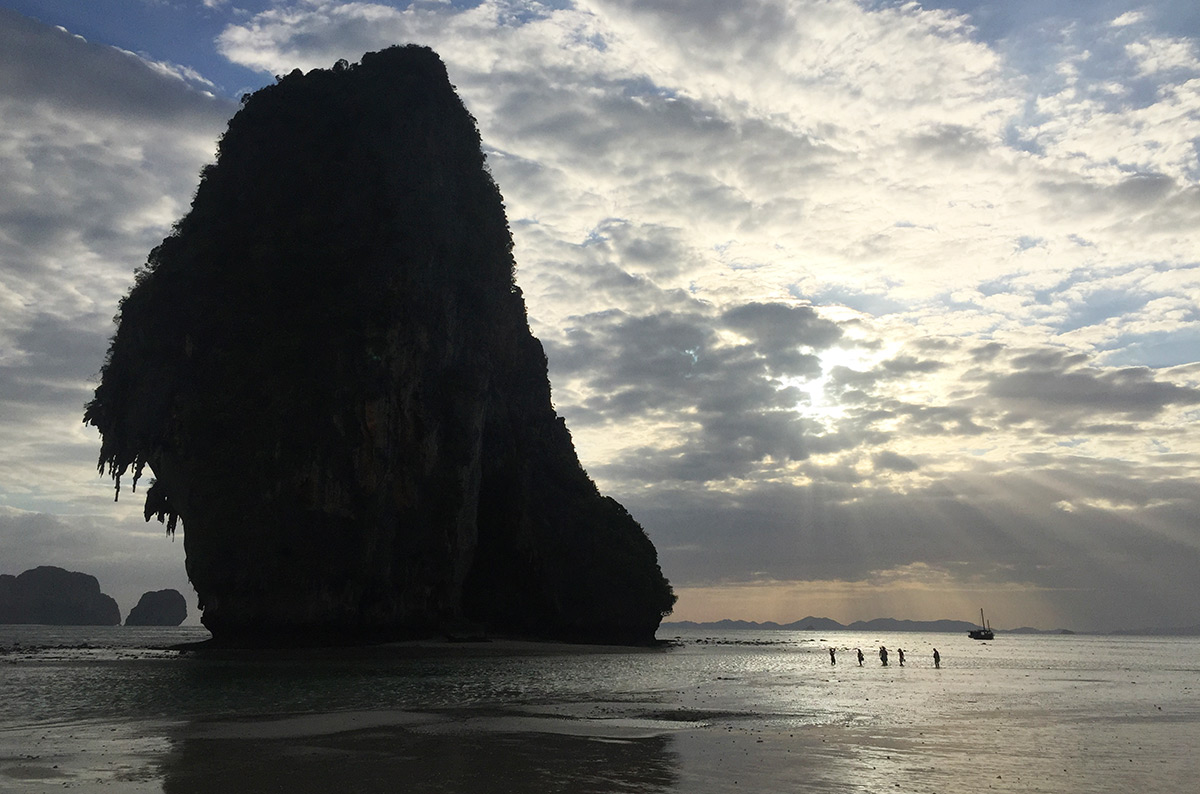 The sun shining through the clouds near a limestone island at Pranang Beach in Thailand