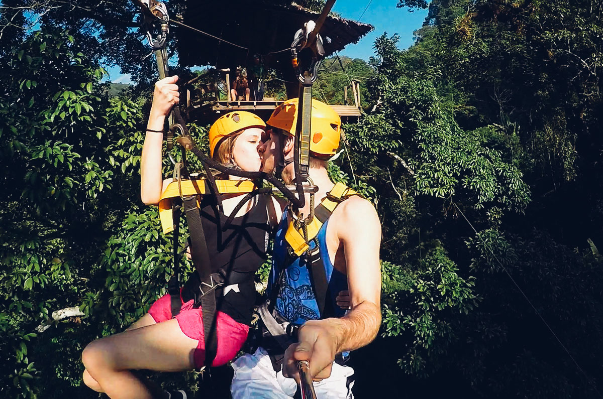 Kissing on the tandem zipline at Flight of the Gibbon in Chiang Mai